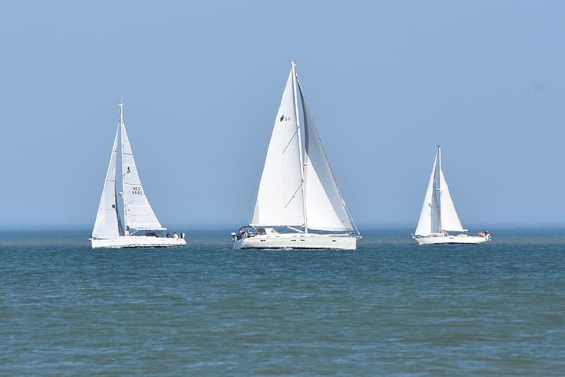 Three white sailboats in the middle of ocean at daytime