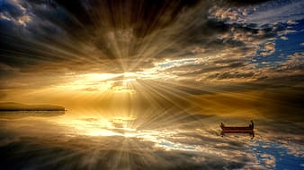 Boat in the middle of the sea during crepuscular rays