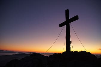 Silhouette of cross on mountain peak during golden hour