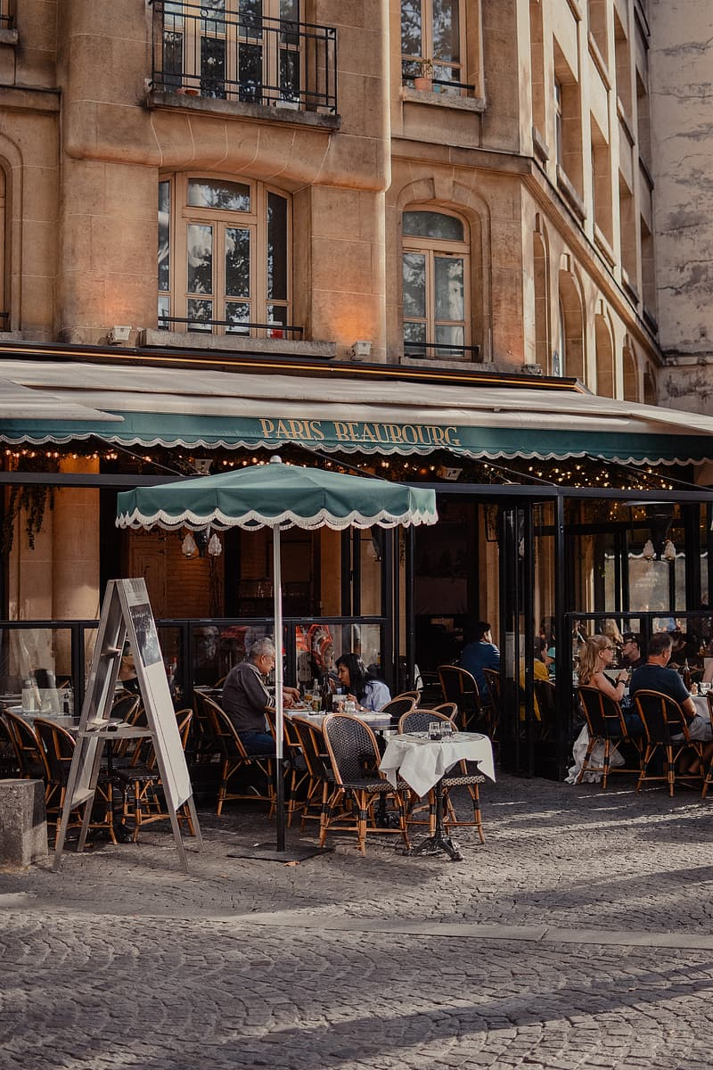 People sitting on chairs outside restaurant during daytime