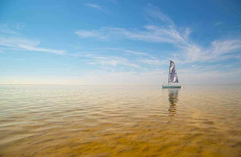 Green sailboat under gray white clouds