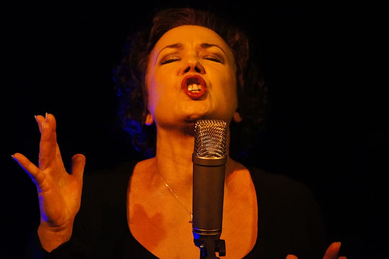 Woman wearing black scoop-neck top singing in front of condenser microphone