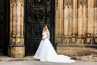 Woman in white wedding dress standing near brown concrete building during daytime
