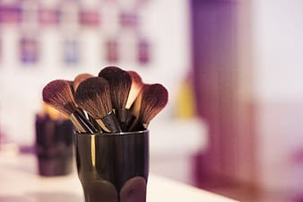 Makeup brush on vase on table top