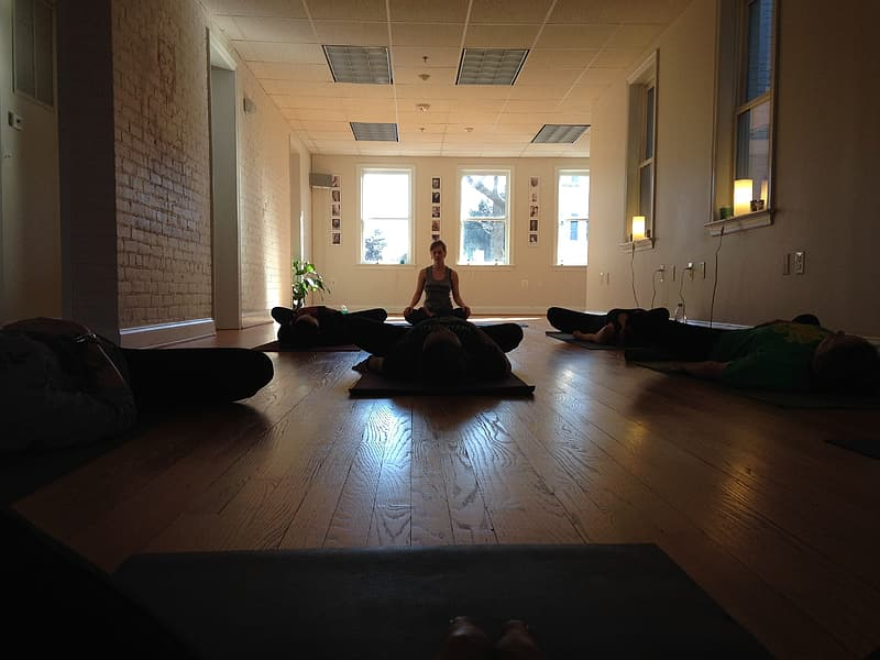 Silhouette of people doing yoga inside brown wooden floor room