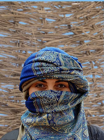 Close up photo of a person wearing blue and green floral scarf