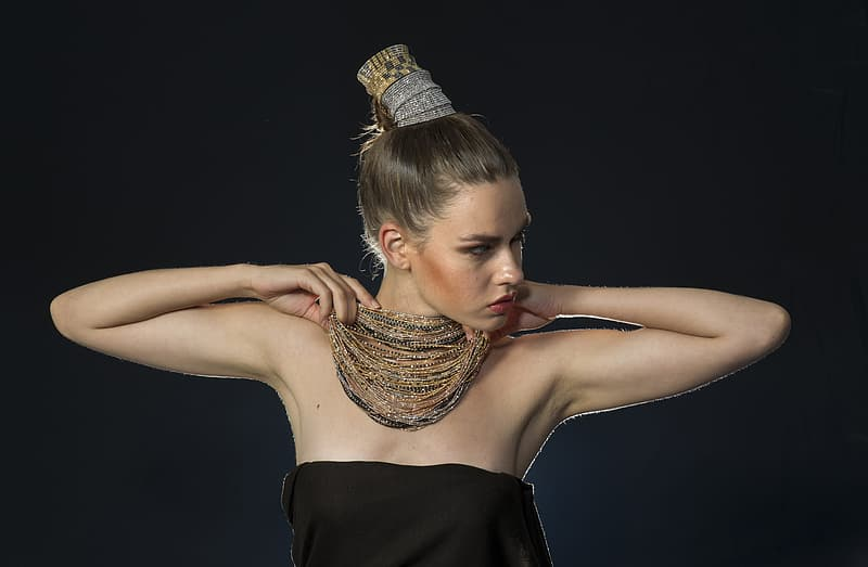 Woman holding gold-colored necklace