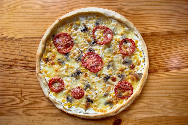 Round pizza with pepperoni on brown wooden table top view photography