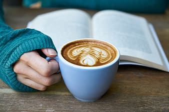 Person holding blue ceramic cup with coffee inside and book behind