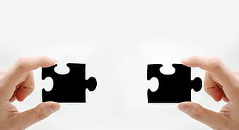 Person holding black two jigsaw puzzles