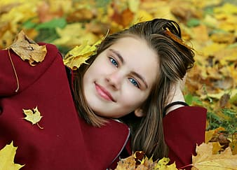 Woman laying in yellow leaf covered field