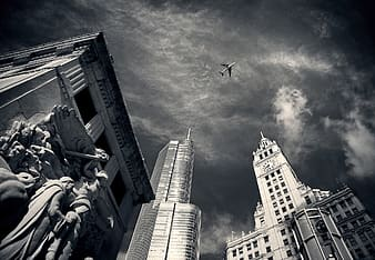 High-rise building over viewing flying airplane low-angle photography