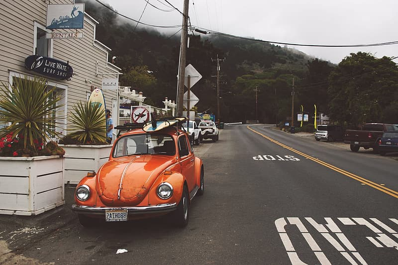 Orange Volkswagen Beetle coupe on road near brown building