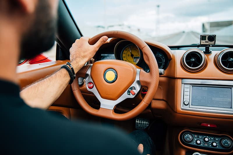 A bearded young man on driving a car with focus on dashboard and steering wheel