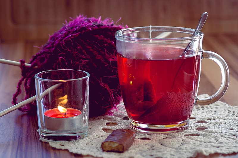 Clear glass mug filled with tea beside clear glass tealight holder and purple fleece textile