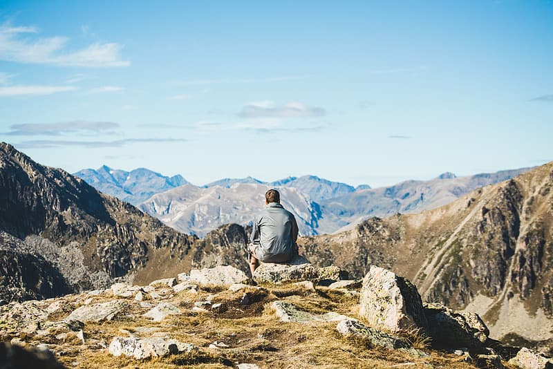 Rear view of a traveler sitting on the edge of a cliff and watching the  mountains | Pikrepo
