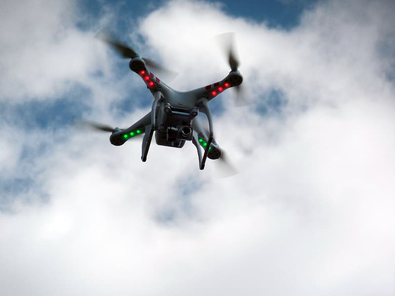 Black and white drone flying under white clouds during daytime