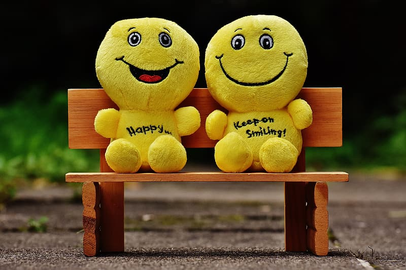 Two yellow emoticon plush toys sitting on brown wooden bench