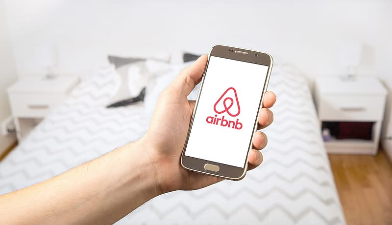 Person holding smartphone displaying Airbnb logo