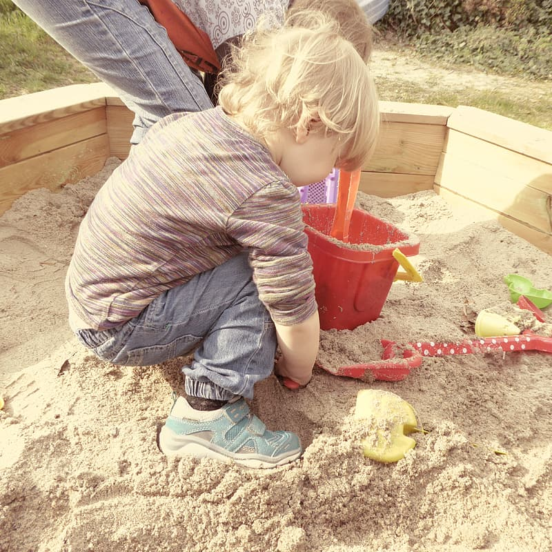 Boy playing on sand during day time