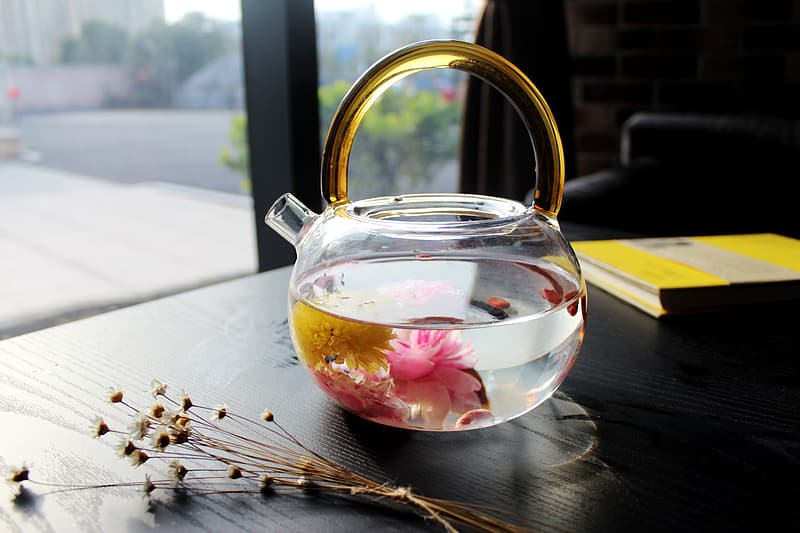 Clear glass kettle on black wooden table