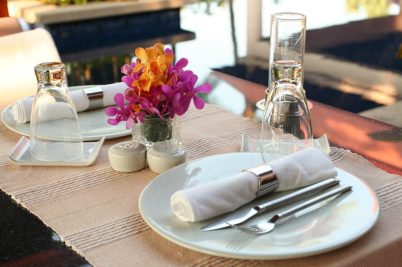 Gray stainless steel spoon and fork in white ceramic plate