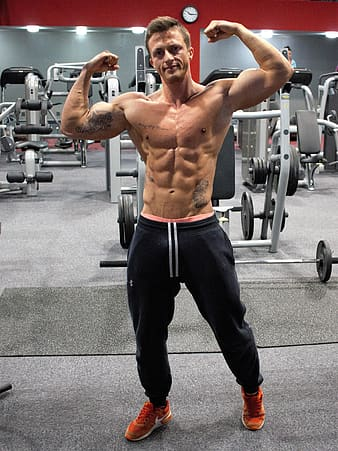 Man flexing his body inside the gym