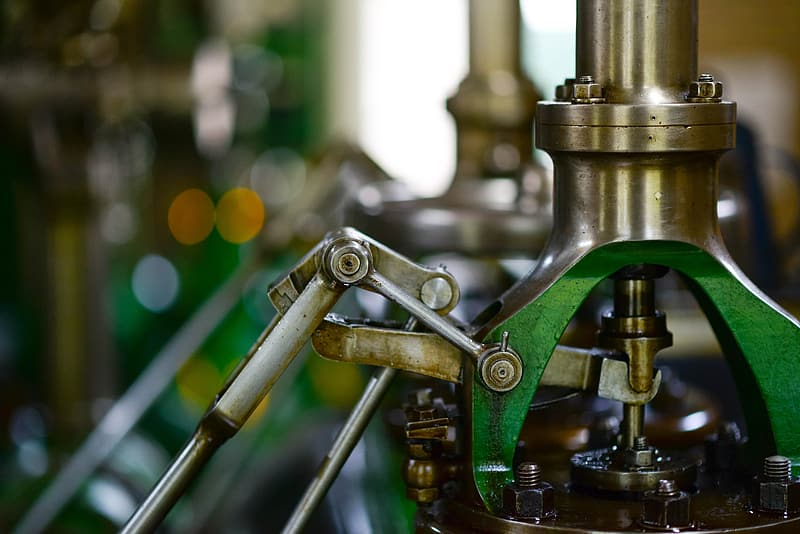 Selective focus photography of green and silver metal machine