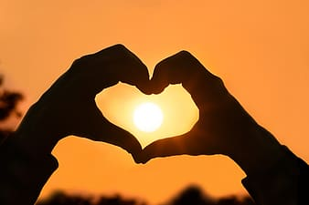Person making a heart shape with hands at sunset