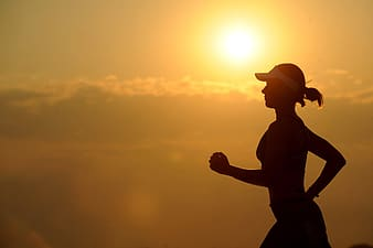 Silhouette of woman running during sunset