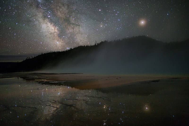Landscape photo of mountain reflecting on body of water during night time