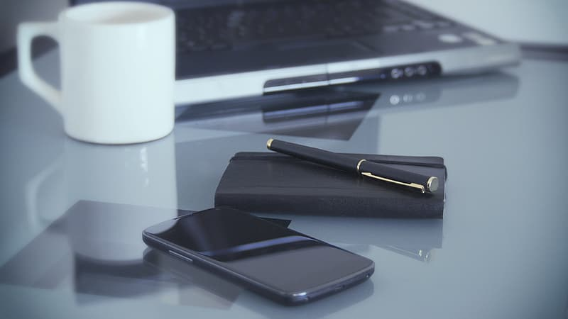 Black smartphone near pen and notebook