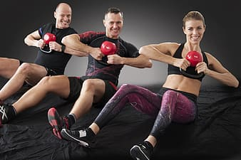 Two men and one woman sitting on carpet holding kettlebell