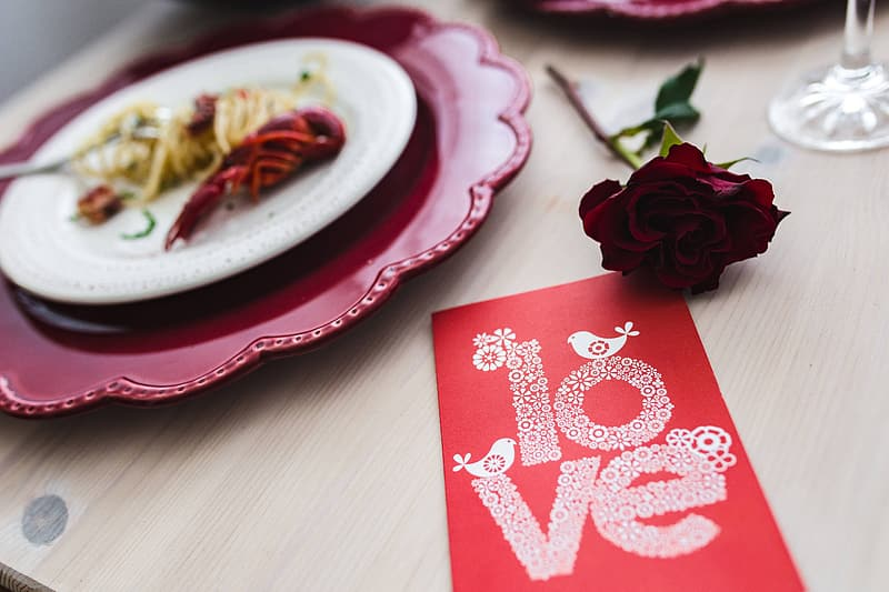Red and white heart print card on brown wooden table