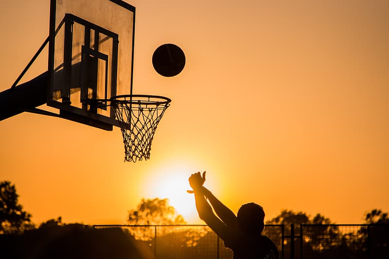 Silhouette photo of a person playing a basketball