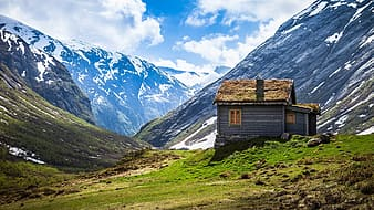 Photo of brown wooden house on top of green hill near snow mountains during day time