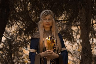 Woman holding bundle of lighted candles