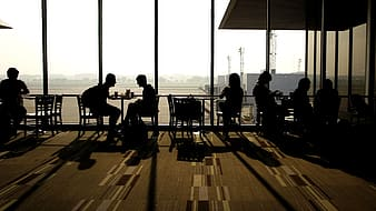 Silhouette of people sitting on chair beside glass wall