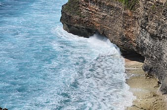 Photography of sea waves on brown cliff