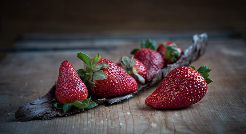 Close up photo of strawberries on brown wooden table