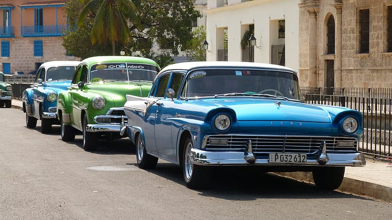 Two blue and one green parked vintage cars