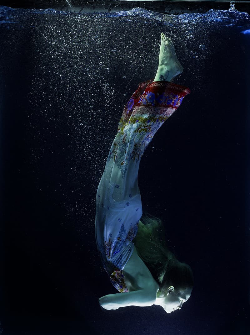 Woman in white, red, and blue dress diving on water
