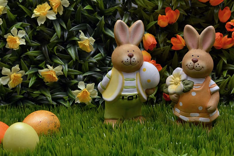 Two brown rabbit figurines on green grass field