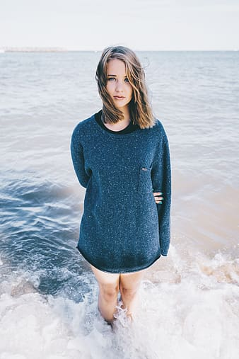 Woman in black long-sleeved shirt standing on body of water