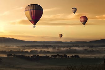 Several hot air balloons above ground photo