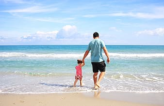 Man holding girl beside seashore