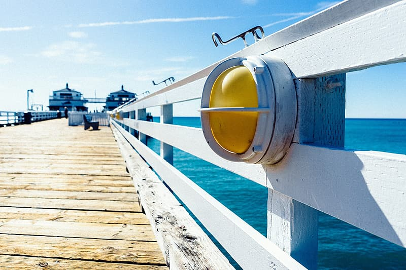 Yellow and white metal bucket on wooden dock during daytime