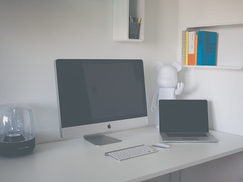 Silver iMac, Apple Wireless Keyboard, and MacBook Pro on desk
