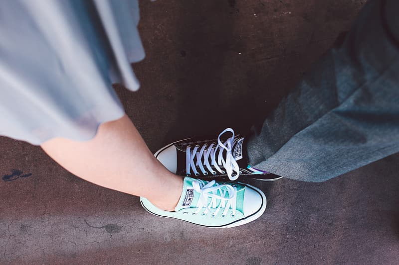 Close up photo of man and woman in teal and black Converse All Star low top sneakers