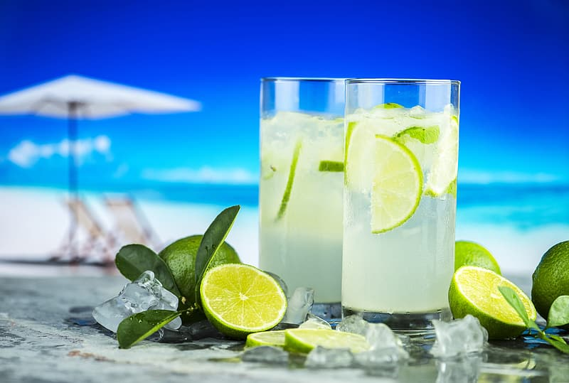 Two clear drinking glass with liquid and lime fruits